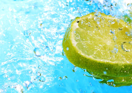 water splash on slices of lemons on blue background photo