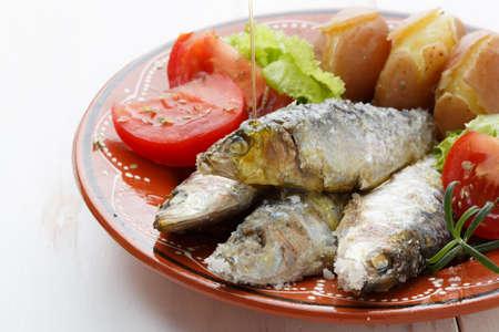 sardinas: aceite de oliva que se vierte en un plato de sardinas