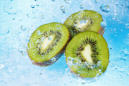 water splashing on kiwi slices-top view photo
