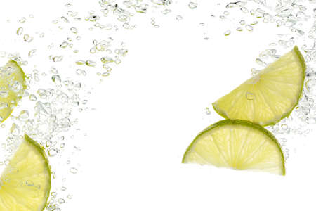 slices of lime in water isolated on white photo