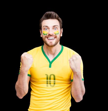 futball: Brazilian fan celebrates on black background