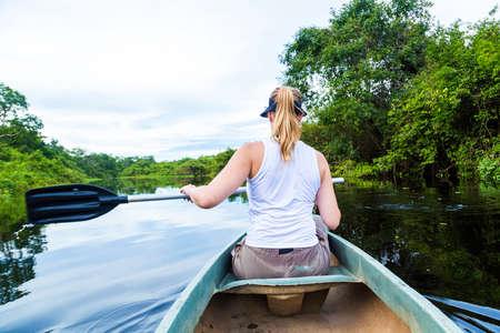 rio amazonas: Mujer que monta en canoa r�o Pantanal, Brasil