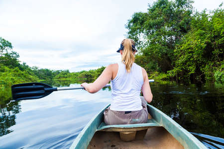 amazon river: Woman riding canoe in Pantanal River, Brazil