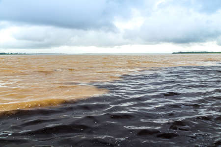 cloud drift: The meeting of waters, a confluence between Rio Negro and the Amazon river