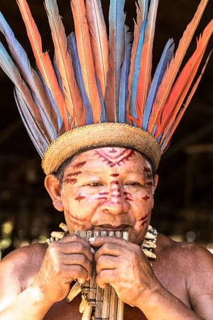 indigenous: Native Brazilian man playing wooden flute at an indigenous tribe in the Amazon