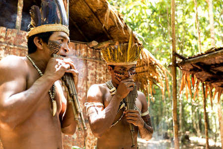 native american man: Native Brazilian guys playing wooden flute at an indigenous tribe in the Amazon Stock Photo