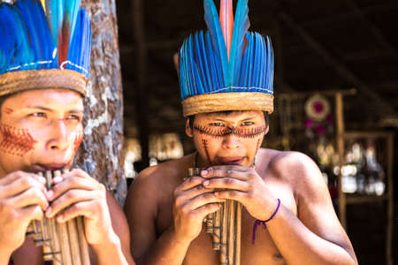 maniac: Native Brazilian guys playing wooden flute at an indigenous tribe in the Amazon Stock Photo