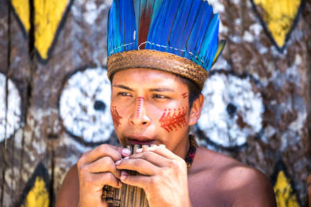 indigenous: Native Brazilian guy playing wooden flute at an indigenous tribe in the Amazon Stock Photo