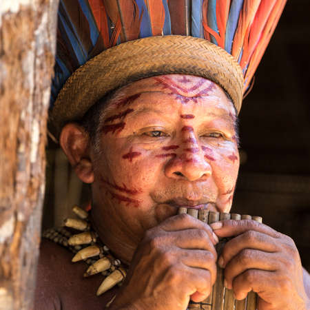 maniac: Native Brazilian man playing wooden flute at an indigenous tribe in the Amazon
