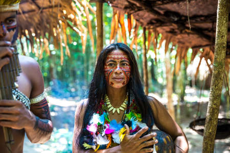 indigenous: Native Brazilian group playing wooden flute at an indigenous tribe in the Amazon Stock Photo