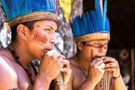 amazon rainforest: Native Brazilian guys playing wooden flute at an indigenous tribe in the Amazon Stock Photo