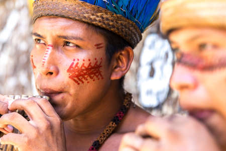 native indian: Native Brazilian guys playing wooden flute at an indigenous tribe in the Amazon Stock Photo