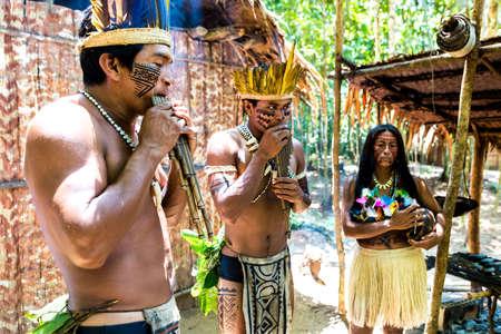 El grupo brasileño nativa que toca la flauta de madera en una tribu indígena en el Amazonas Foto de archivo