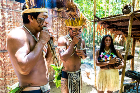 Native Brazilian group playing wooden flute at an indigenous tribe in the Amazon Stock Photo
