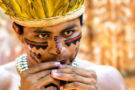maniac: Native Brazilian guy playing wooden flute at an indigenous tribe in the Amazon Stock Photo