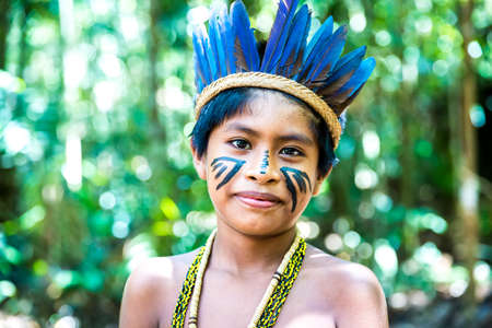 native american man: Native Brazilian boy playing wooden flute at an indigenous tribe in the Amazon Stock Photo