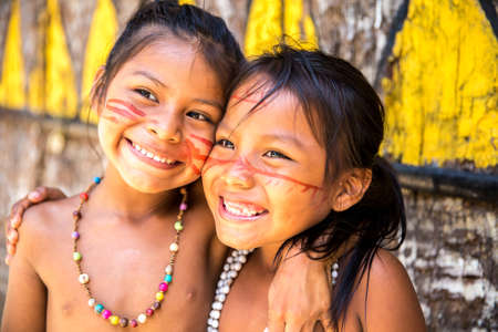 village: Native Brazilian girls smiling at an indigenous tribe in the Amazon