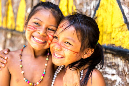 culture: Native Brazilian girls smiling at an indigenous tribe in the Amazon