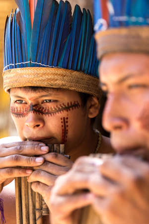 native american man: Native Brazilian guys playing wooden flute at an indigenous tribe in the Amazon Editorial