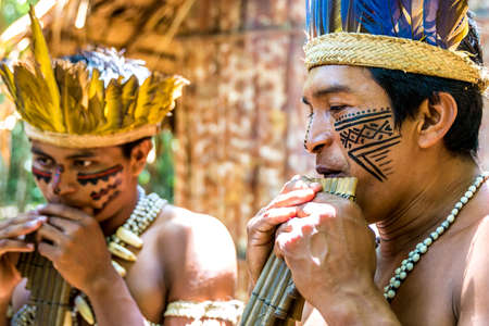 indigenous: Native Brazilian men playing wooden flute at an indigenous tribe in the Amazon Stock Photo