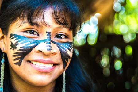 indigenous: Native Brazilian girl smiling at an indigenous tribe in the Amazon Editorial