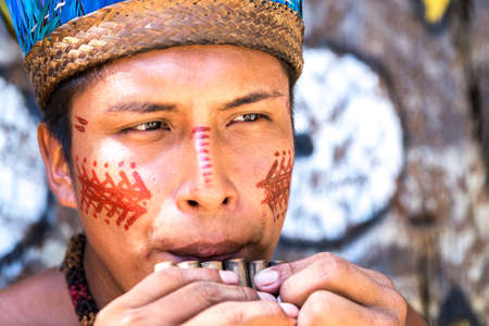 indigenous: Native Brazilian guy playing wooden flute at an indigenous tribe in the Amazon.