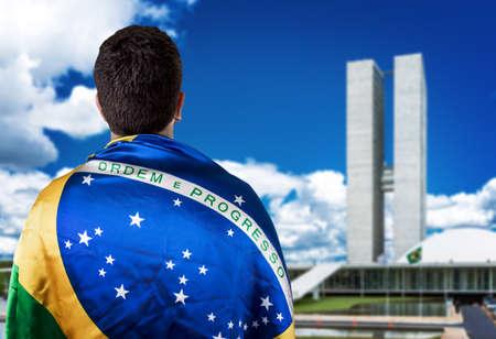 winning flag: Man holding the Brazilian flag in Brasilia