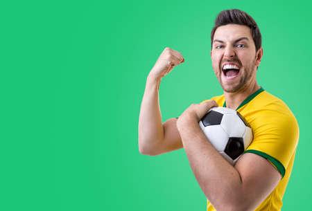 maniac: Brazilian male fan celebrating on green background. Stock Photo