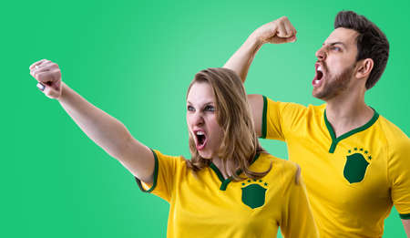 Brazilian couple fans celebrating on green background Stock Photo