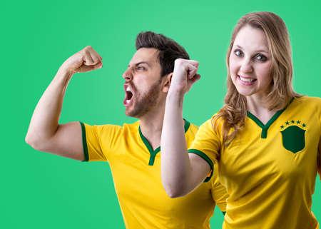 futball: Brazilian couple fans celebrating on green background Stock Photo