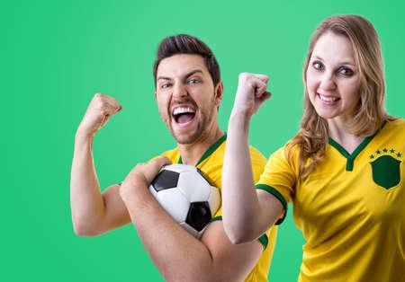 maniac: Brazilian couple fans celebrating on green background Stock Photo