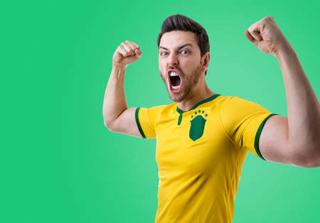 Brazilian male fan celebrating on green background. Stock Photo