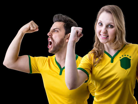 futball: Brazilian couple celebrating fan on black background Stock Photo