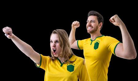 maniac: Brazilian couple celebrating fan on black background Stock Photo