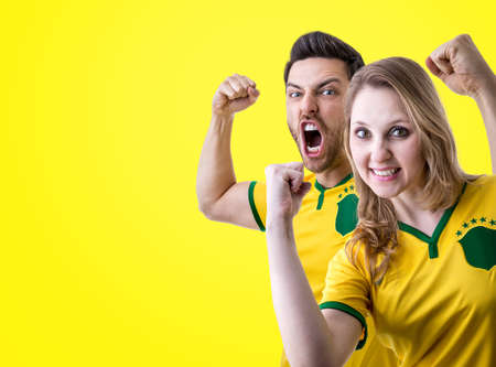 Brazilian couple fans celebrating on yellow background