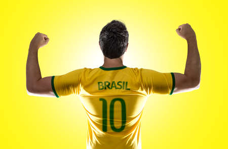 Brazilian male fan celebrating on yellow background Stock Photo