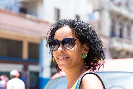 mujeres morenas: La cubana y un viejo coche rojo en La Habana, Cuba