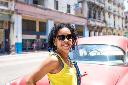 femmes souriantes: femme cubaine et une vieille voiture rouge à La Havane, Cuba