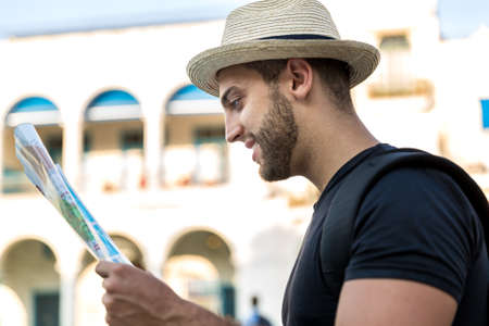 finding a mate: Tourist consulting a city guide searching locations in the street Stock Photo