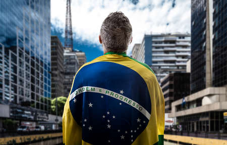 Brazilian man holding the flag of Brazil in Sao Paulo
