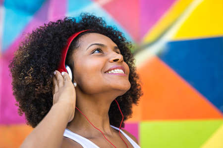 dreadlock: Afro woman listening to music on colourful background