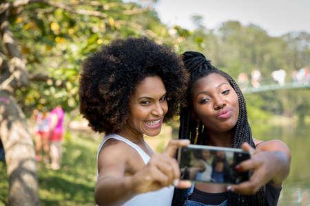 femmes souriantes: amis Afro ayant plaisir à prendre des photos de selfie dans le parc Banque d'images