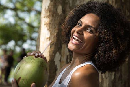 mujer alegre: Mujer brasileña beber agua de coco en el parque Foto de archivo