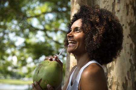 afro woman: Brazilian woman drinking coconut water in the park