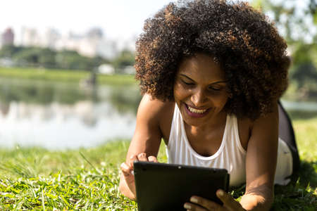 woman outdoor: Brazilian woman using computer tablet in the park