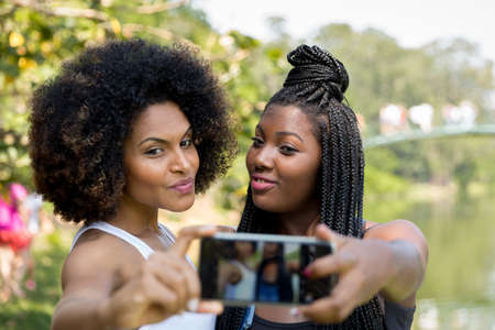 portrait of a women: Afro friends having fun taking selfie photos in the park
