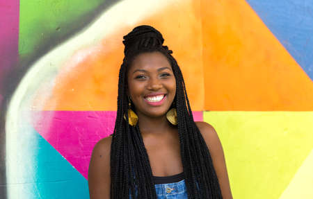brazilian woman: Portrait of Young Afro Brazilian woman smiling on colorful background Stock Photo