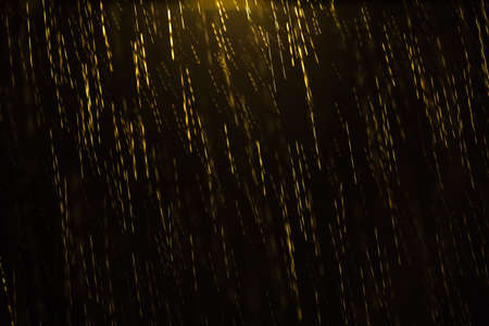 convey: Night shot of a golden colored rain illuminated from the top by a lamp post with motion blur and droplets in focus and out of focus giving the sensation of depth. Can be used as a background, pattern or texture and to convey emptiness, solitude and loneli