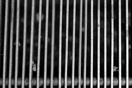 hard bound: Black and white dirty grill with a bar hiding more out of focus dirt behind it. Concept and abstract image that can be used to stop corruption, theft, fraud (any other bad thing) and acting like a prison, jail for them protecting the society of this dirty