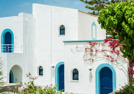 Greek architecture - white buildings, sea and blue windows, Bougainvillea on the wall Stock Photo